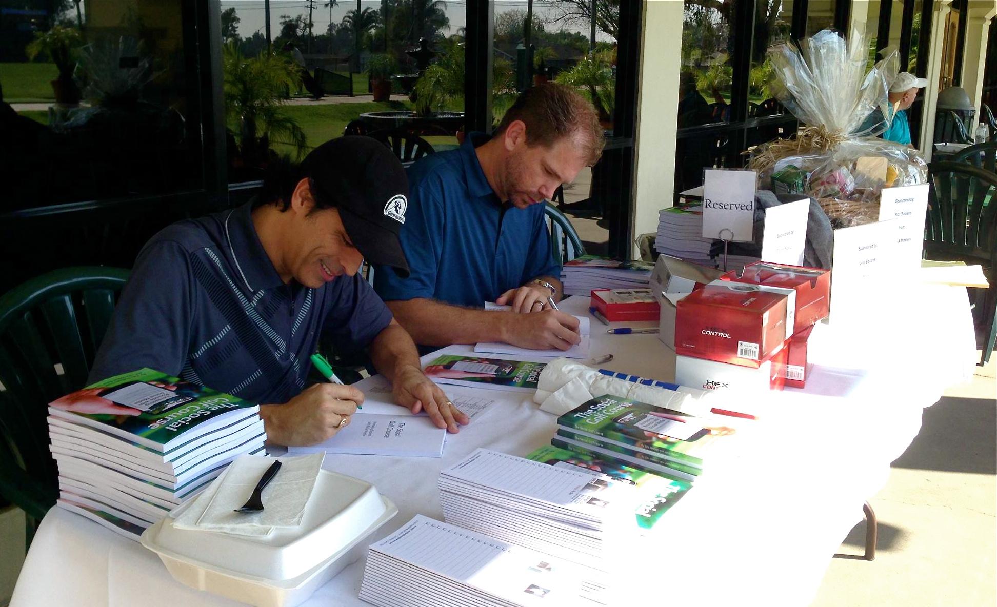 Zeb and John sign The Social Golf Course book